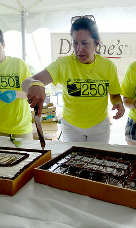 JIM VAIKNORAS/Staff photo Mayor Donna Holaday cuts the city birthday cake at the Newburyport 250th Clam Bake at Plum Island point Sunday afternoon.