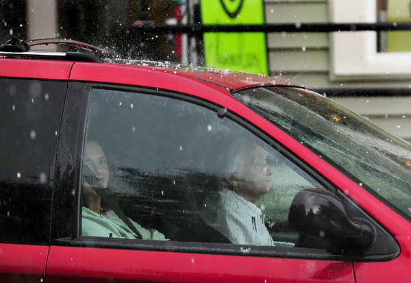 BRYAN EATON/ Staff Photo. Hail drops on the van of these two ladies waiting out the storm on Liberty Street in Newburyport yesterday afternoon.