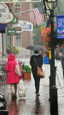 BRYAN EATON/Staff Photo. There were plenty of people with umbrellas and raincoats in downtown Newburyport as the rain came down heavy at times yesterday. The weather improves for the weekend, though some rain could return late Sunday.