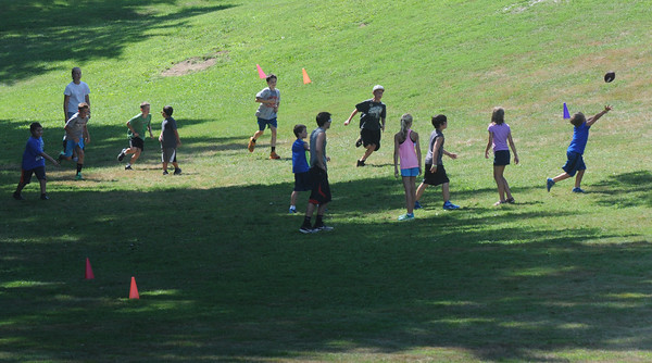 BRYAN EATON/Staff Photo. Youngsters play a casual game of football in a shaded area of Amesbury Town Park on Monday. They are in the summer program at the Amesbury Recreation Department which ends on Friday.