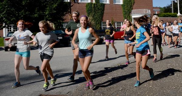 BRYAN EATON/Staff Photo. Newburyport High girls cross country team heads out along High Street.