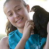 JIM VAIKNORAS/Staff photo Volunteer Maddie Soucy holds a chicken at teh petting zoo at Family Day in Maudslay Saturday.