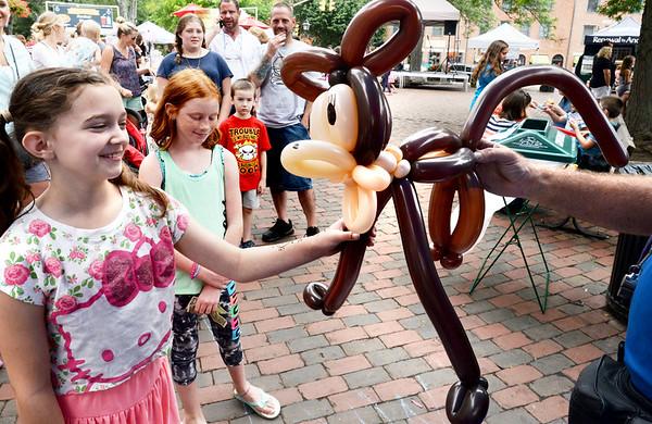 BRYAN EATON/Staff photo. Haley Cotter, 10, of Newburyport takes her balloon monkey made Mr. Dee in Newburyport's Market Square.