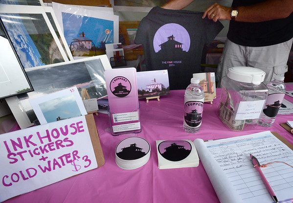 """Bryan Eaton/Staff photo. Several items are for sale at the booth in Inn Street to save the """"pink house"""" on Plum Island Turnpike."""