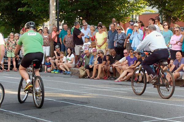 BRYAN EATON/Staff photo. Spectators line Pleasant Street to watch the second celebrity heat of the Slow Bike Race.