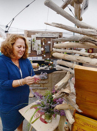 BRYAN EATON/Staff photo. Barbara Tomkins of Foraged, her business in North Andover, makes original home decor from reclaimed materials as driftwood, glass and even things people leave out on the roadside for the taking. She was at Market Square Craft Show.