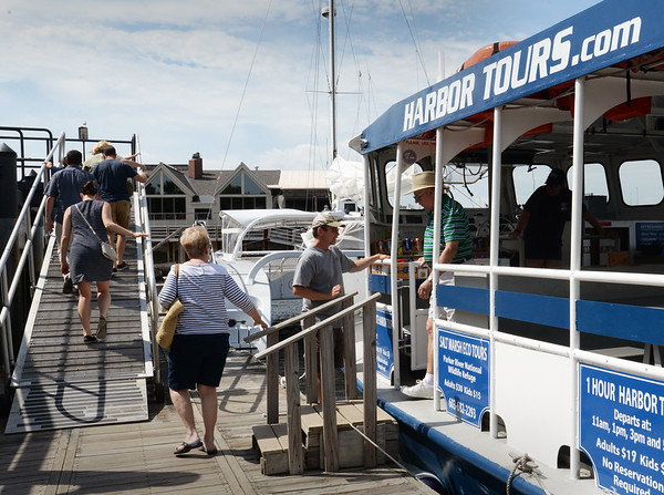 BRYAN EATON/Staff photo. Norman Clark, skipper of Yankee Clipper Harbor Tours bids adieu to customers as they disembark yesterday at the Newburyport waterfront.