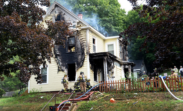 BRYAN EATON/Staff photo. The lone occupant of this home at 82 Congress Street in Amesbury was taken to the hospital with burns after a two-alarm fire heavily damaged the residence. A candle is thought to be the possible cause of the blaze.