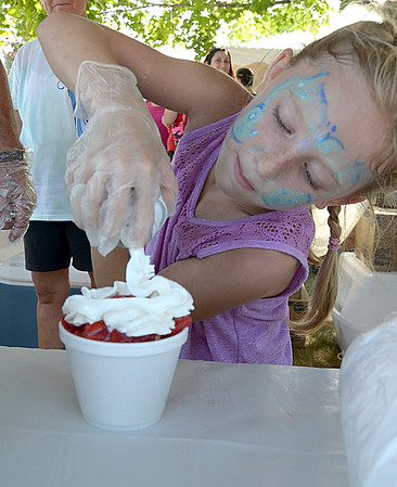 JIM VAIKNORAS/ Staff photo Kasie Coleman, 7, puts wiped cream on top of a strawberry shortcake being sold by the Four Corners Church Seabrook Old Home Days Saturday at Seabrook Middle School.