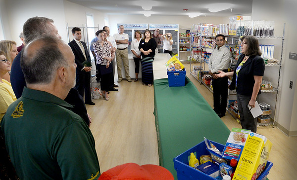 BRYAN EATON/Staff photo. Seabrook selectman chairman Aboul Khan looks on as Donna Lee of Rockingham County Action welcomes guests in the food pantry of their new facility on Route 1 in Seabrook yesterday.
