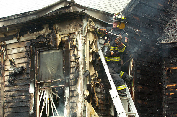 BRYAN EATON/Staff photo. A firefighter clears vinyl siding looking for hotspots on the second story of the home.