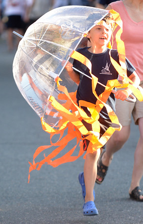 JIM VAIKNORAS/Staff photo. Mateo Cueto-Potts uses a umbrella tp mimic a jellyfish runs with Merrohawk down Federal Street in the annual Lions Club Bed Race.