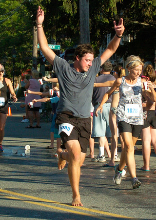 BRYAN EATON/Staff photo. One runner in bare feet shows his excitement for running in the 5K race.