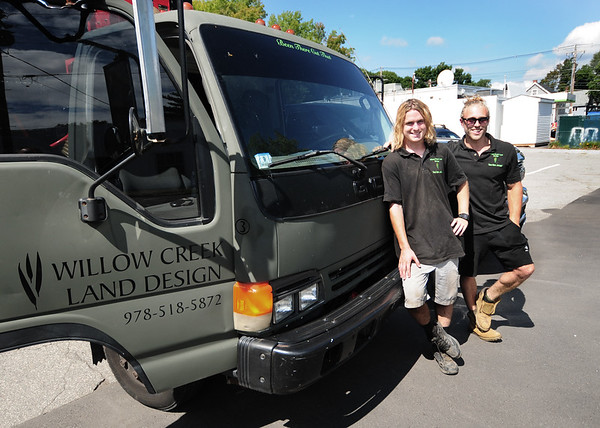 JIM VAIKNORAS/Staff photo Jeremy Robidoux,owner of Willow Creek Land Design,on right, and one of his employees Brian Landergan with their trucks in Amesbury.