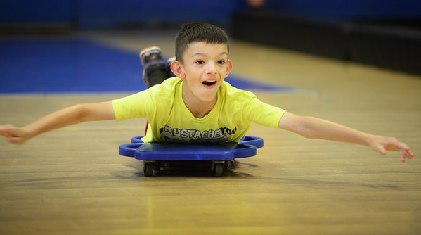 BRYAN EATON/Staff photo. Riley Stevens, 10, of Amesbury moves along on two scooters in a relay game at the Boys and Girls Club in Salisbury on Monday afternoon. The club is doing Olympic events all week to coincide with the games in Rio de Janeiro.
