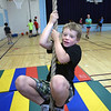 BRYAN EATON/Staff photo. Oliver Shakespeare, 10, swings on one of the ropes at the Brown School gym Wednesday morning. Clipper Kids and Clipper Crew summer programs with the Newburyport Youth Services were moved there from the Perkins Playground due to the rain.