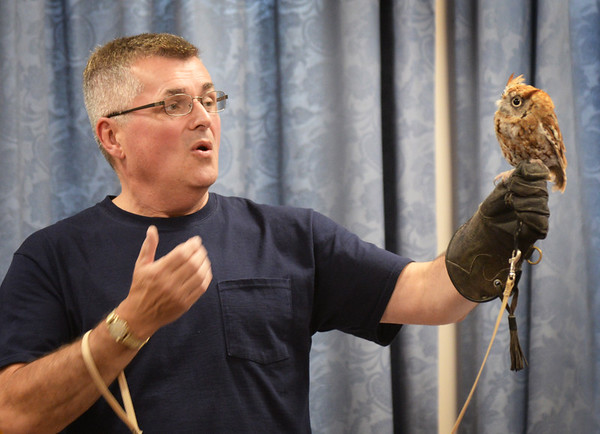 BRYAN EATON/Staff photo. Jim Parks of Wingmasters shows a screech owl at Heritage Tower in Amesbury. The Amesbury Public Library collaborated with the Amesbury/Merrimac Housing Authority for the program bringing younsters and senior citizens together for the presentation.