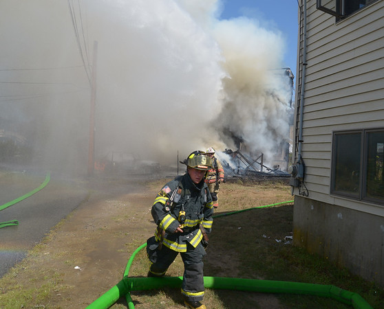 JIM VAIKNORAS/Staff photo Firefighter runs back to a truck while battling a blaze on on Plum Island Saturday afternoon.