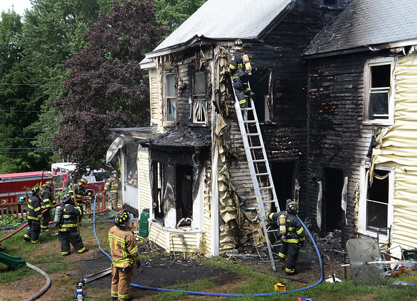 BRYAN EATON/Staff photo. Firefighters from Amesbury and surrounding communities check for hot spots in a two-alarm fire that heavily damaged a three story home at 82 Congress Street in that town.