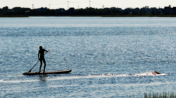 JIM VAIKNORAS/Staff photo A stand up paddle boarder is silhouette against the morning sky as he escorts a swimmer on Joppa Flats Sunday.
