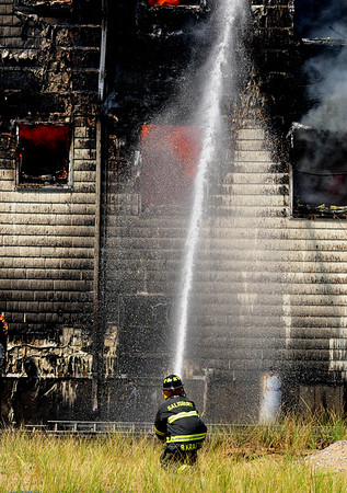 JIM VAIKNORAS/Staff photo A Salisbury firefighter pours water on a fire on 20th Street on Plum Island.