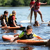 BRYAN EATON/Staff photo. Anthony Kataxinos, 9, moves along at Camp Kent on Lake Gardner in Amesbury during paddleboarding and swimming time at the town's Recreational Department's Summer Camp where they had been kayaking earlier. In the water will be the place to be the next couple days at the temperature will reach into the 90's along with some humidity.