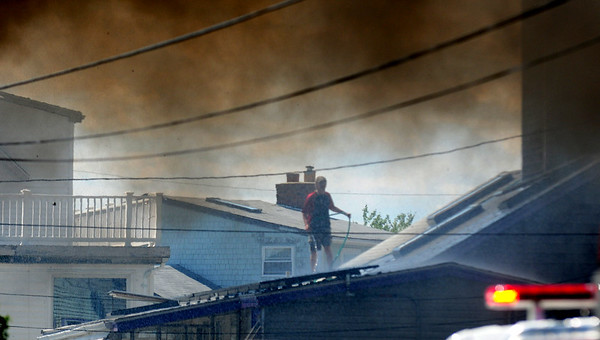JIM VAIKNORAS/Staff photo  A man pours water on his roof can be seen through the smoke of a fire on 20th Street on Plum Island.