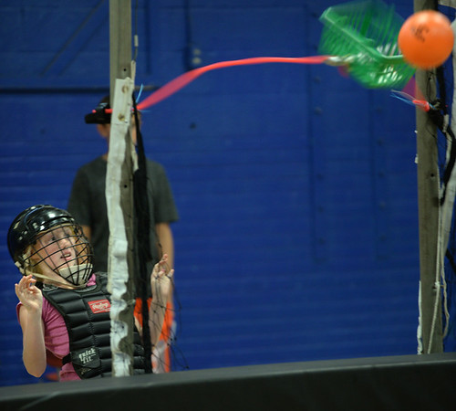 BRYAN EATON/Staff photo. Destiny Cronin-Choquette, 10, of Amesbury releases a ball on a giant slingshot aimed at Boys and Girls Club director Jim Keenan who was firing tennis balls at her. They were playing American Gladiator on Wednesday and she got to station five before she got hit.