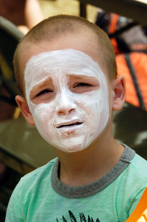 BRYAN EATON/Staff photo. Silas Corning, 4, of Andover has his face painted with a white base before getting the rest of the black paint for his skeleton mask at Kids Day in the Park.