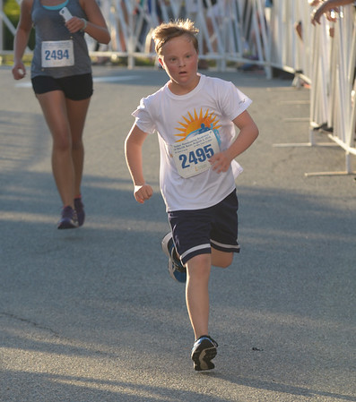 JIM VAIKNORAS/Staff photo Runner Ben St. Lawrence crosses the finish line at the Lions Club Yankee Homecoming 5k in Newburyport.