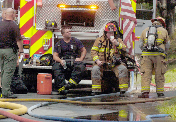 BRYAN EATON/Staff photo. Firefighters rehydrate after attacking a house fire at 82 Congress Street in Amesbury late Tuesday afternoon.