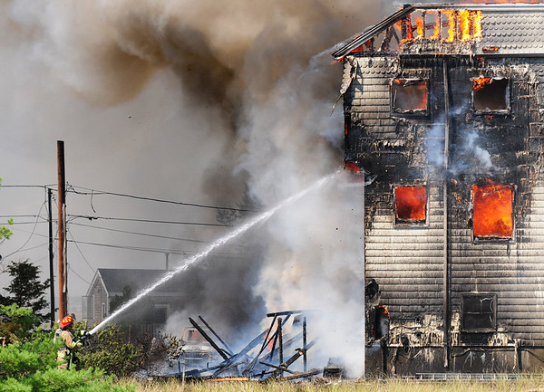 JIM VAIKNORAS/Staff photo A Newburyport firefighter pours water on a fire on 20th Street on Plum Island.