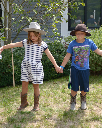 JIM VAIKNORAS/ Staff photo Stella Pelletier, 8, and her brother Simon, 6, help build a human chain around the Rowley Library to give it a hug as they celebrate it's 125 birthday Saturday.