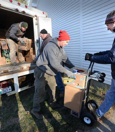 BRYAN EATON/Staff photo. Volunteers for the First Parish Church of Newbury's Food Pantry unload a truck where they picked up goods from the Boston Food Bank.