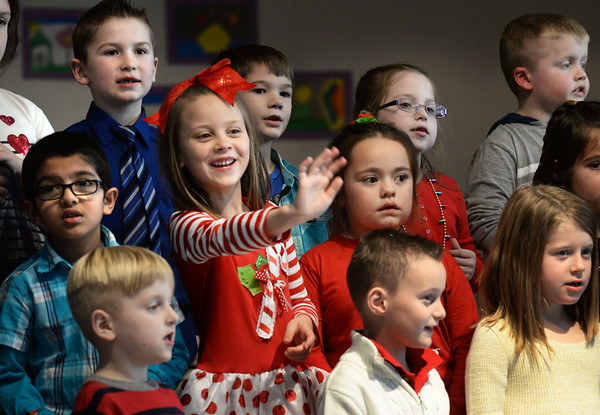"""BRYAN EATON/Staff photo. Sherry Snow, 6, stops singing """"Rudolph The Red-Nosed Reindeer"""" long enough to wave at family members sitting in the cafeteria at Salisbury Elementary School on Monday afternoon. She and her fellow first-graders were performing in a Christmas Holiday Sing-a-long."""