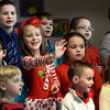"BRYAN EATON/Staff photo. Sherry Snow, 6, stops singing ""Rudolph The Red-Nosed Reindeer"" long enough to wave at family members sitting in the cafeteria at Salisbury Elementary School on Monday afternoon. She and her fellow first-graders were performing in a Christmas Holiday Sing-a-long."