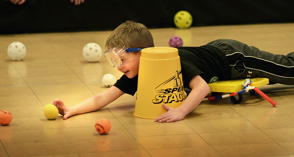 """BRYAN EATON/Staff photo. Matthew Jovilet, 7, of Amesbury is one of four in a game of """"Hungry Hippo"""" at the Boys and Girls Club on Wednesday afternoon. The children move into a corraled area on a scooter to grab as many balls as they can in a certain time before being yanked back to the corner."""
