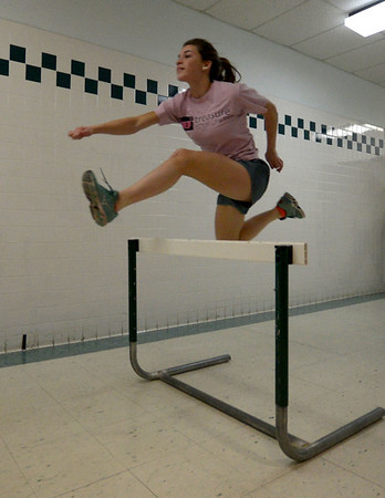 JIM VAIKNORAS/Staff photo Belle Smith practices the hurtles in a hall way during  Pentucket High School girls track practice.