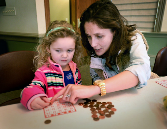 BRYAN EATON/Staff photo. Scarlett DeJordy of Newburyport gets help from her mother, Katie, while playing bingo at the Newburyport Public Library, one of the school vacation week activities there. It was a fun way to win prizes as well as learn numbers for the four-year-old.