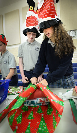 """BRYAN EATON/Staff photo. The Immaculate Conception School in Newburyport opened a """"Christmas Store"""" in the gymnasium on Monday and Tuesday afternoons. Students could buy different items with proceeds going to the school and the eighth grade class volunteered to wrap the gifts. Owen Reid, left, and Kate Herndon, both 13, wrap several blankets for William Bean, 8."""