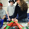 "BRYAN EATON/Staff photo. The Immaculate Conception School in Newburyport opened a ""Christmas Store"" in the gymnasium on Monday and Tuesday afternoons. Students could buy different items with proceeds going to the school and the eighth grade class volunteered to wrap the gifts. Owen Reid, left, and Kate Herndon, both 13, wrap several blankets for William Bean, 8."