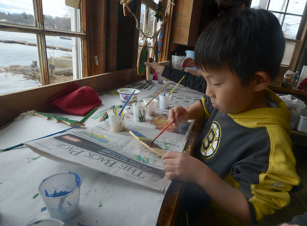 JIM VAIKNORAS/ staff photo Isaac Gilbert, 7, paints a wooden ornament at the annual Holiday Open House at Lowell Boat shop in Amesbury this weekend. Along with wood crafts the event included an art sale, silent auction, chowder, and live music.