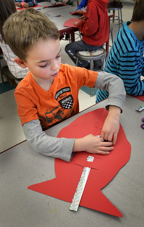"""BRYAN EATON/Staff photo. Jaxon Palladino, 7, slides a strip of sparkly foil through the cut-out of a fish in Amy Merluzzi's art class at Newbury Elementary School on Tuesday afternoon. She joked with the children who were learning how to weave as she sang """"We Fish You a Merry Christmas."""""""