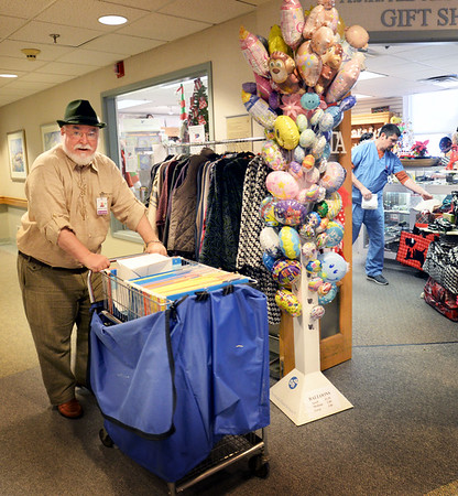 BRYAN EATON/Staff photo. Jonathan Meath, who plays Santa Claus in soft drink commercials, also volunteers to deliver mail at the Anna Jaques Hospital, heads into the gift shop.