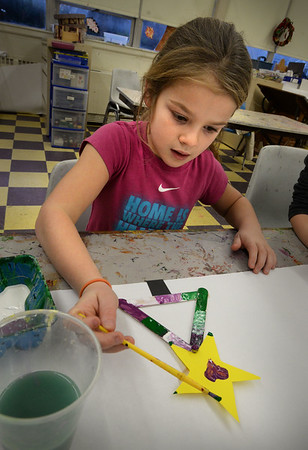 BRYAN EATON/Staff photo. Youngsters in the arts and crafts room at the Boys and Girls were making Christmas ornaments on Monday afternoon. Star Mispilkin, 7, of Newburyport finishes painting hers before sprinkles were added for more sparkle.