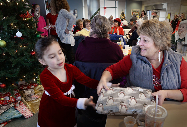 BRYAN EATON/Staff photo. The Amesbury Senior Center hosted their annual Christmas Breakfast with Santa Claus giving out presents and jazz music on Tuesday morning. Santa's helper Reita Willey, 5, delivers a gift to an apreciative Sabie Randall, both of Amesbury.