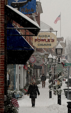 JIM VAIKNORAS/Staff photo Shoppers brave the snow Saturday morning as they make their way down State Street in Newburyport.