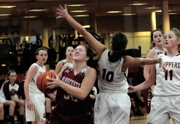 JIM VAIKNORAS/Staff photo Gloucester'sWhitney Good is fould by  fight through the defense of Newburyport's #10 Paige Gouldthorpe during their game at Newburyport High school Wednesday night.
