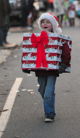 JIM VAIKNORAS/Staff photo Connor Calderwood , 9, dressed as a present as he marched  Saturday afternoon at Amesbury's annual Santa Parade.