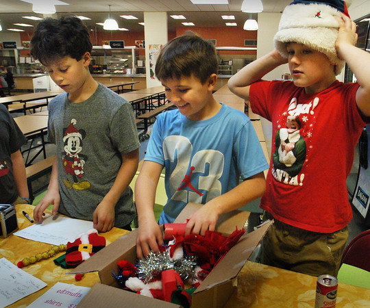 BRYAN EATON/Staff photo. Three Molin Upper Elementary School students decided to make elf costumes and accessories to sell to fellow students to raise money for Toys For Tots. Selling their handiwork during lunch on Thursday, from left, Carson Gretz, Drew Newman and Jack Smith, all 10.